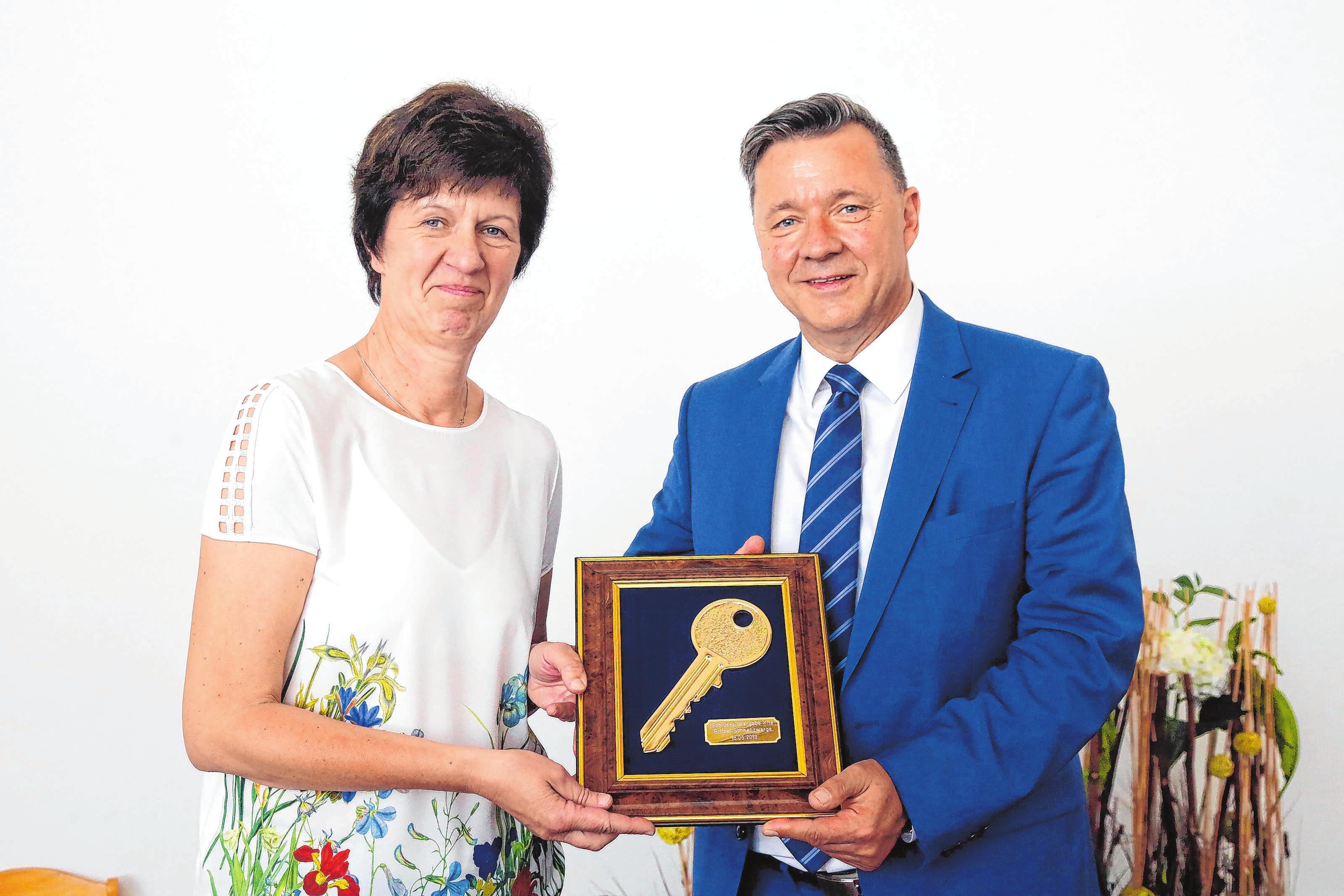 Britz' Bürgermeister André Guse übergibt einen großen symbolischen Schlüssel an die stellvertretende Kita-Leiterin Birgit Thielemann.