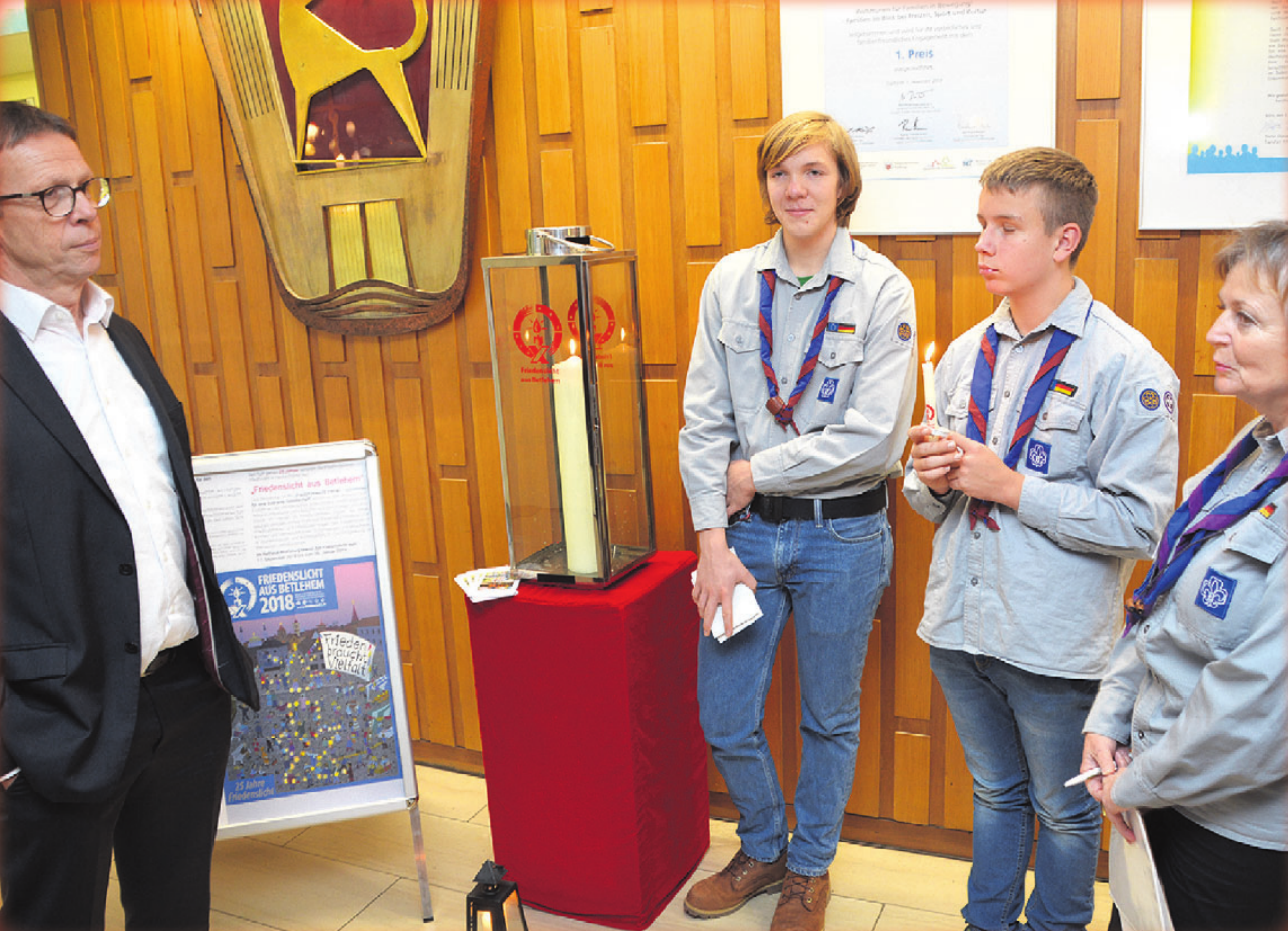 Oberbürgermeister Klaus Mohrs nahm das Friedenslicht von Erik Bennat (16), Jonathan van de Kraan (15) und Therese Zimkowsky (von links) entgegen.