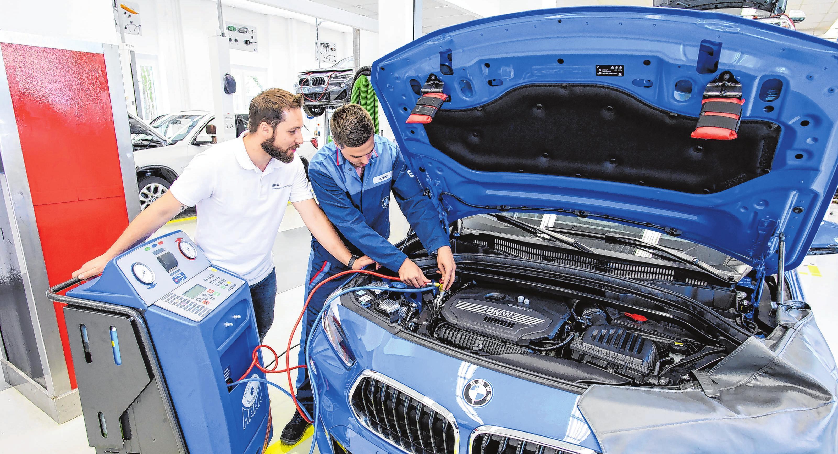 Am Anfang ihrer Ausbildung arbeiten angehende Kfz-Mechatroniker bei BMW meistens unter Anleitung. Hier zeigt Ausbilder Florian Pachur (l) Azubi Andreas Batki, wie man die Klimaanlage eines BMW X2 betankt.