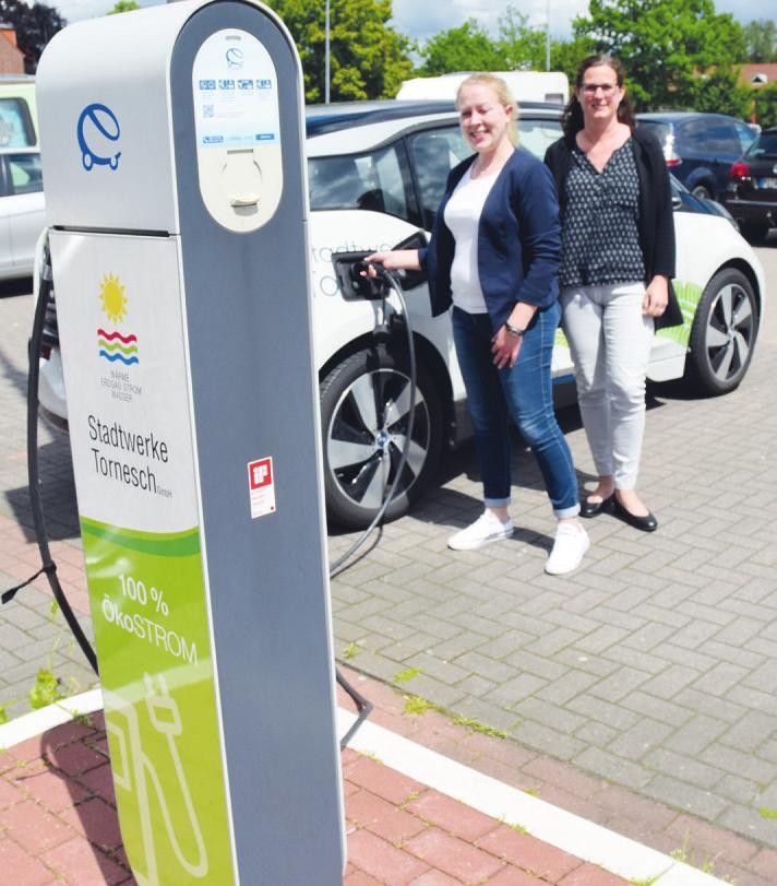 Johanna Köhler (r.) und Esther Jobmann von den Stadtwerken Tornesch präsentieren die Ladestation des Unternehmens auf dem Parkplatz am BahnhofsplatzFoto: Kuno Klein