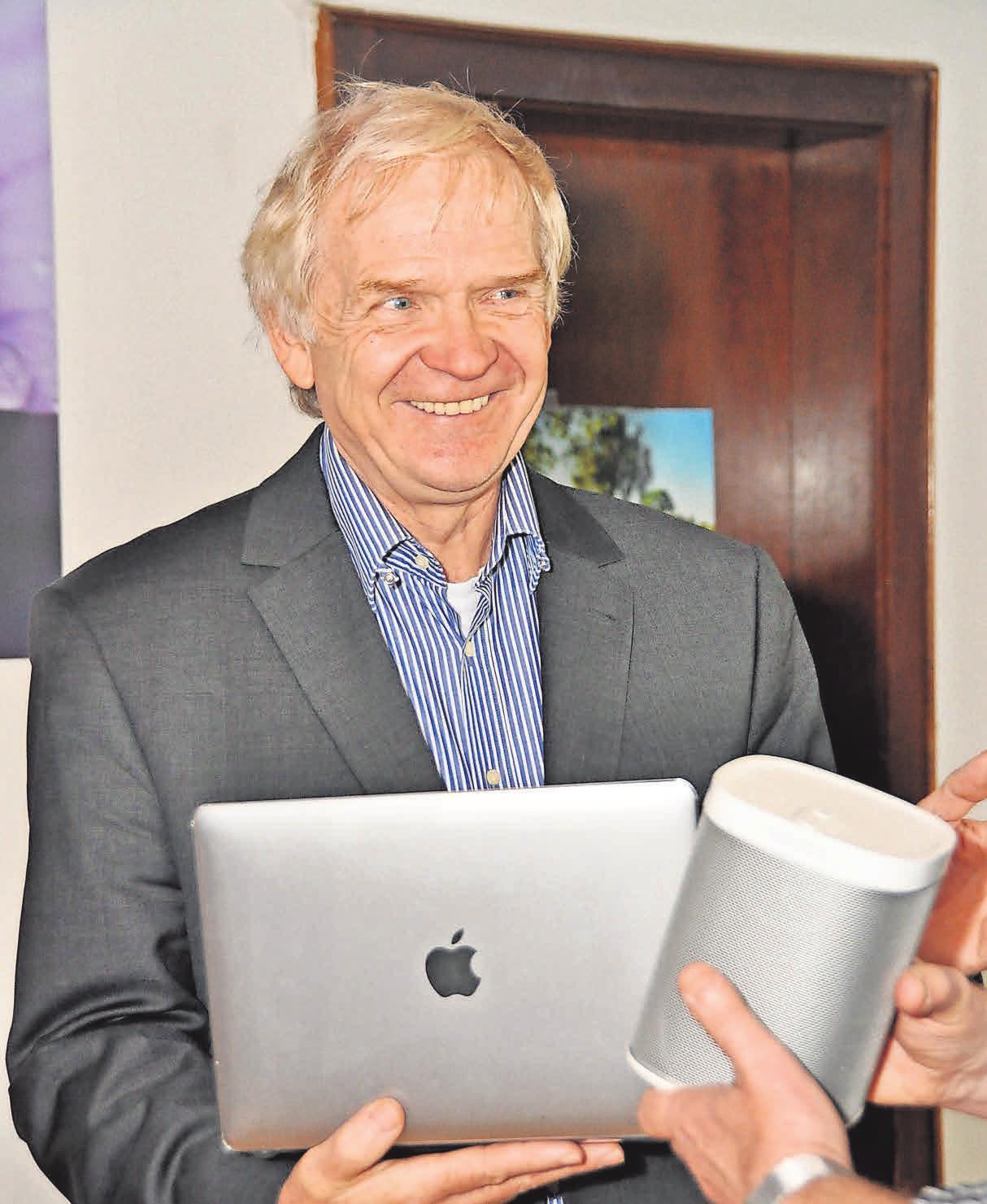 Heinz Mensing überreicht einem Kunden dessen neue Geräte, unter anderem einen Apple-Laptop. Die Auswahl im Lager des Unternehmens lässt keine Wünsche offen.Foto: Archiv