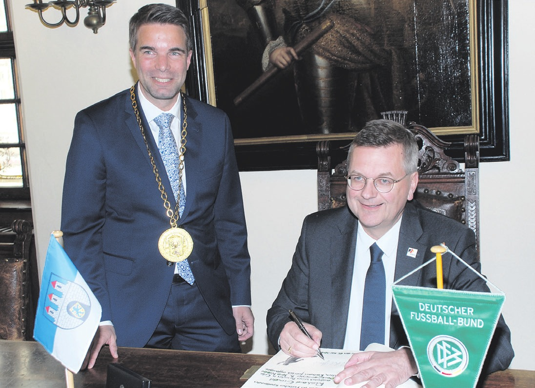 DFB-Präsident Reinhard Grindel (rechts) trug sich ins Goldene Buch der Stadt Celle ein
