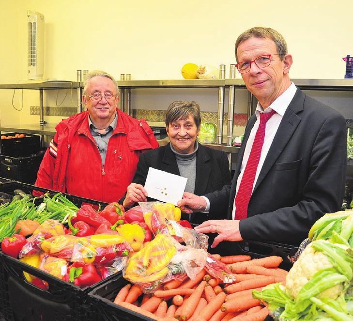 Ortsbürgermeister Detlef Conradt, Tafelchefin Elke Zitzke und OB Klaus Mohrs (v. l.) bei der symbolischen Übergabe des Geschenks in der Sortierstelle der Tafel.