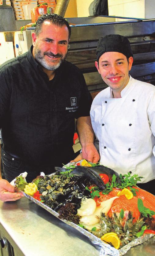 Die La Stazione Fischplatte eine der beliebten Spezialitäten des Hauses - präsentiert von Chef Francesco und Koch Emanuele
