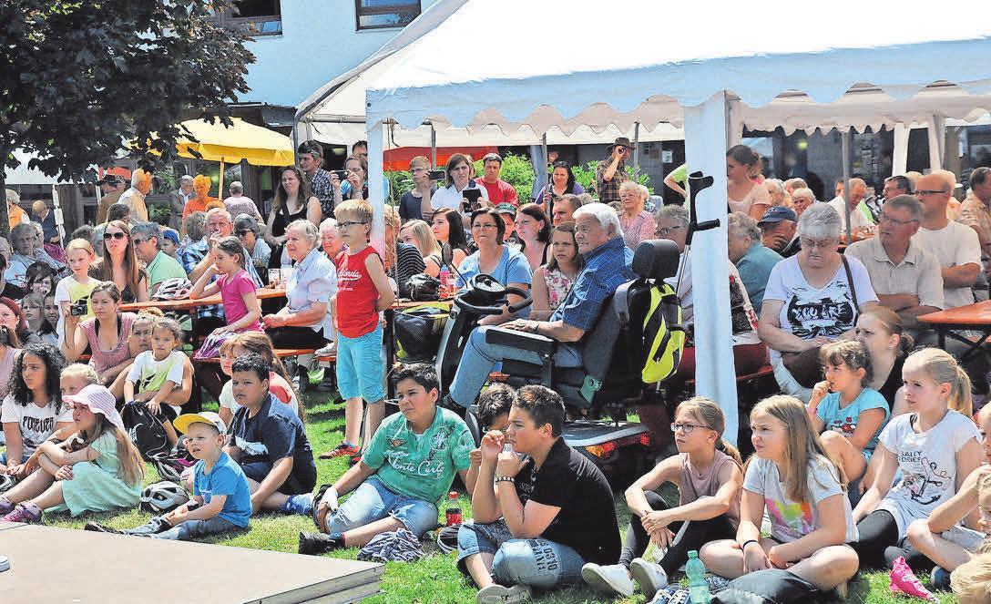 Auf dem Gelände vor dem Rosemarie-Nieschlag-Haus genießen die Zuschauer das Bühnenprogramm. Foto: Katja Eggers
