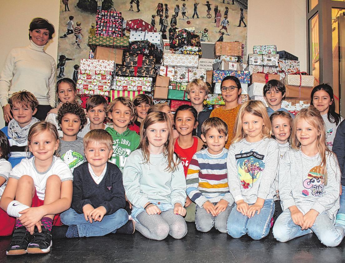 Die Klassensprecherinnen und Klassensprecher und die Leiterin der Grundschule Knauerstraße, Corinna Jorden, vor den mehr als 160 Weihnachtspäckchen für Kinder in Osteuropa Foto: Hanke