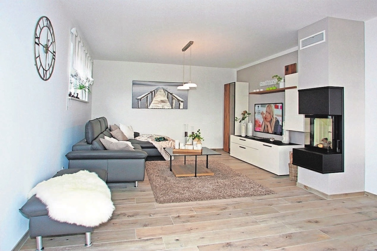 Blick in das helle, gemütliche Wohnzimmer mit Kamin.