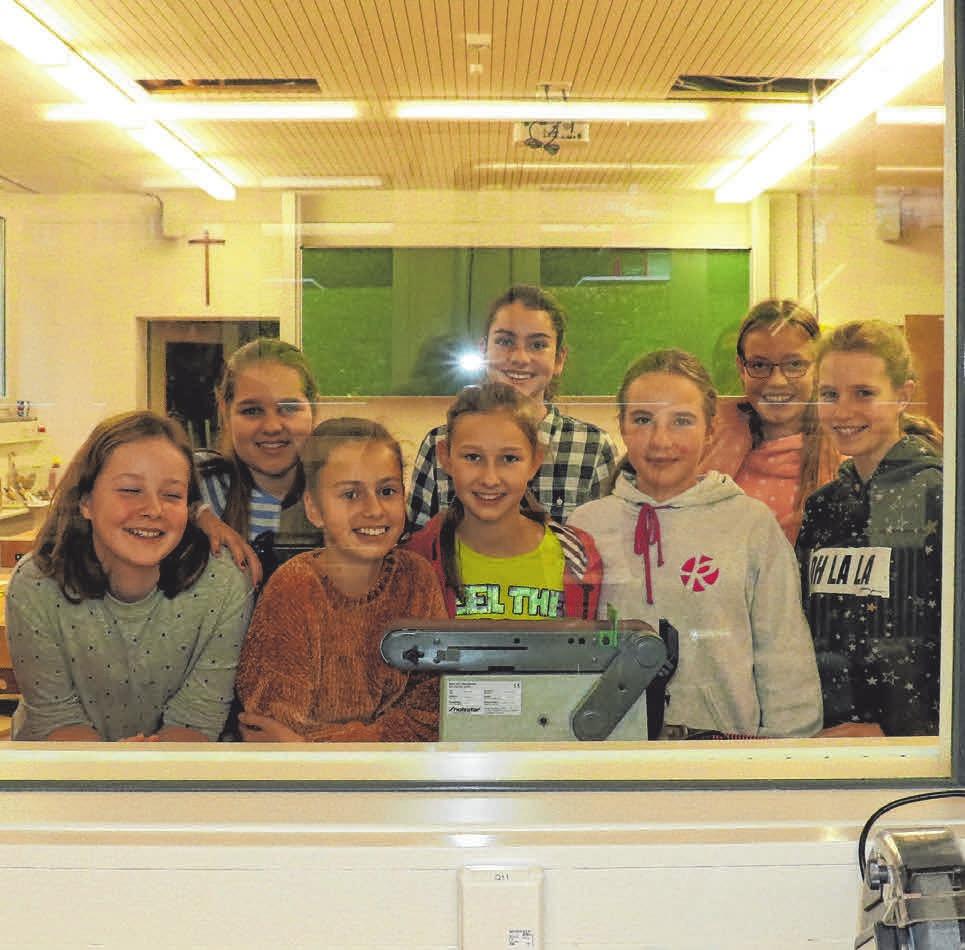 Die Schülerinnen der Klasse 7b beobachten seine Arbeit durch das Sichtfenster.