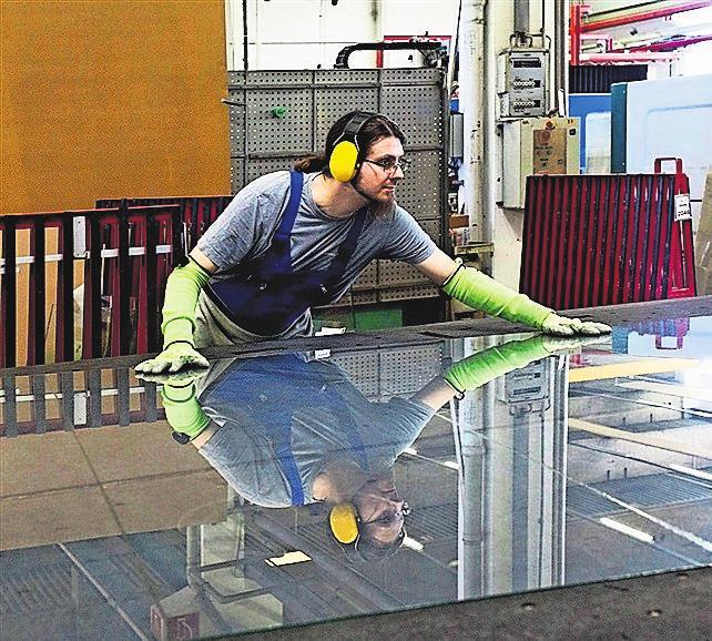 In der Werkstatt schneidet der Glaser eine Glasplatte auf die vorgegebenen Maße