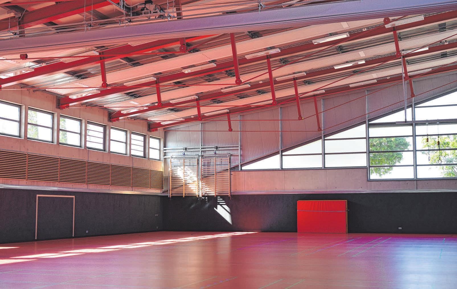 Rote Töne und Holzelemente geben der Sporthalle einen freundlichen Charakter.