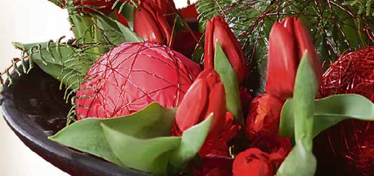 Durch Deko-Elemente wie Kugeln gibt man einem Tulpengesteck den weihnachtlichen Anstrich. Foto: TulpenZeit