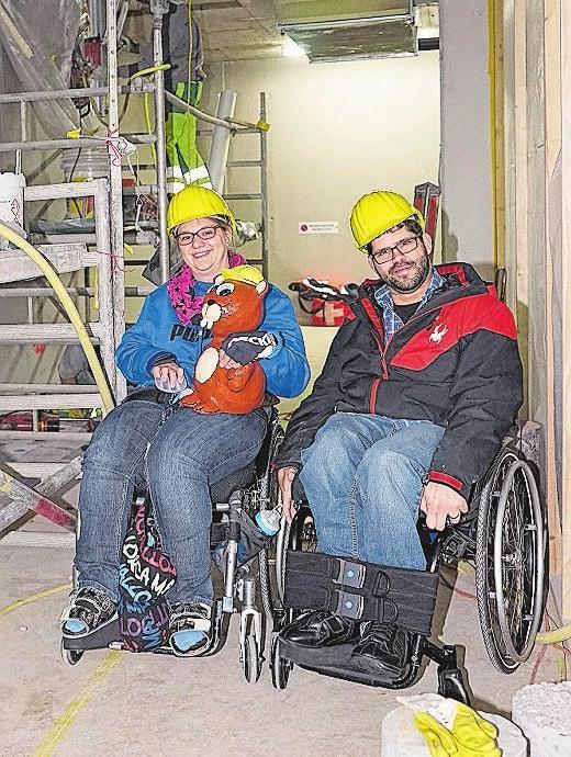 Eine Bewohnerin und ein Mitarbeiter gemeinsam mit Maskottchen Neubi zu Besuch auf der Baustelle des WBZ-Neubaus.
