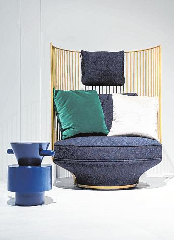 Die Sitzgelegenheit aus der Serie Paradise Bird des Herstellers Wittmann hat statt einer Rückenlehne einen Korb aus dünnen Stäben, in dem gemütliche Kissen liegen.