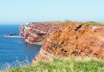 """Die Roten Felsen und die """"Lange Anna"""" im Hintergrund sind Wahrzeichen Helgolands"""