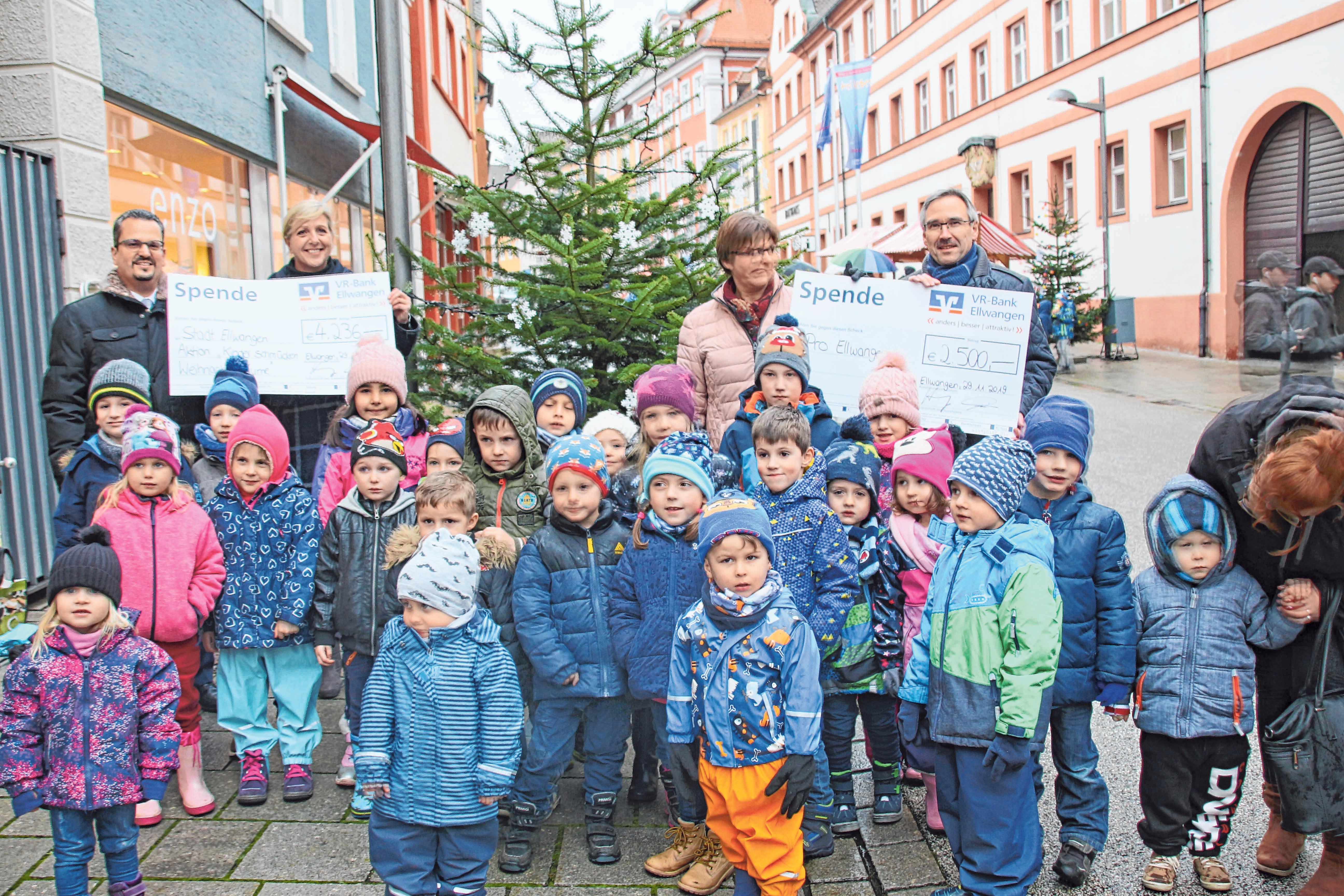 Einen von 63 Weihnachtsbäumen hat der Kindergarten Sankt Martin vergangenen Freitag in der Ellwanger Innenstadt geschmückt. Auf dem Foto zu sehen sind (von links): Bernd Finkbeiner (VR-Bank), Citymanagerin Verena Kiedaisch, Kindergartenleiterin Regina Mayer, Jürgen Hornung (VR-Bank) und die Kindergartenkinder. FOTO: AS