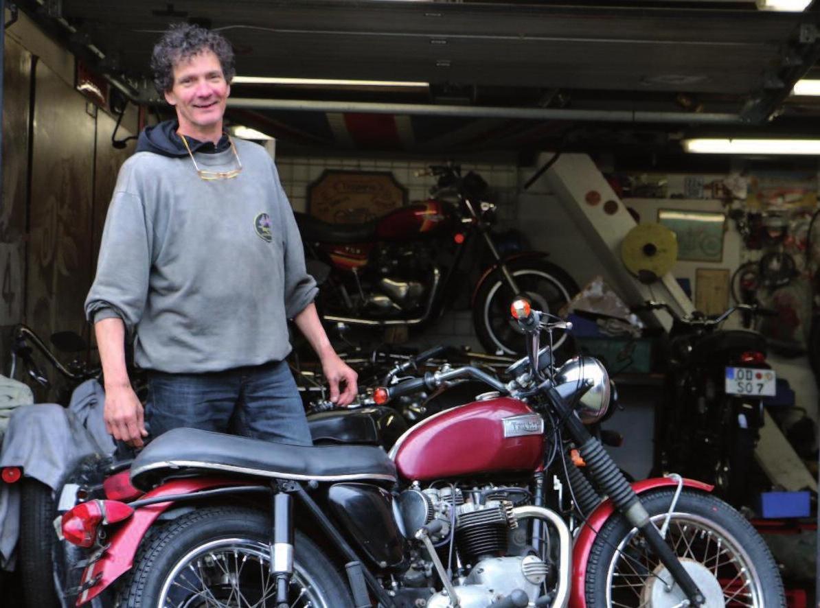 Motorradkenner Steffan Hamer mit einer Triumph Bonneville von 1969 vor seiner prall gefüllten Garage. Fotos (3): Dirk Mangartz