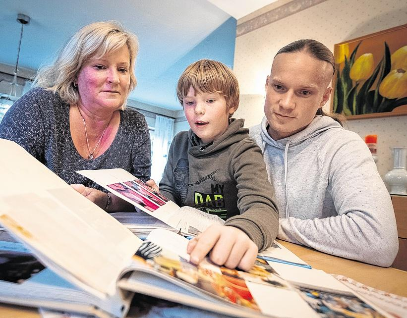 Gemeinsam stöbern Oma Anke Hartmann, Vater Martin und Sohn Falco in den alten Fotoalben zu Martins Geburt. FOTO: VOLKER BOHLMANN