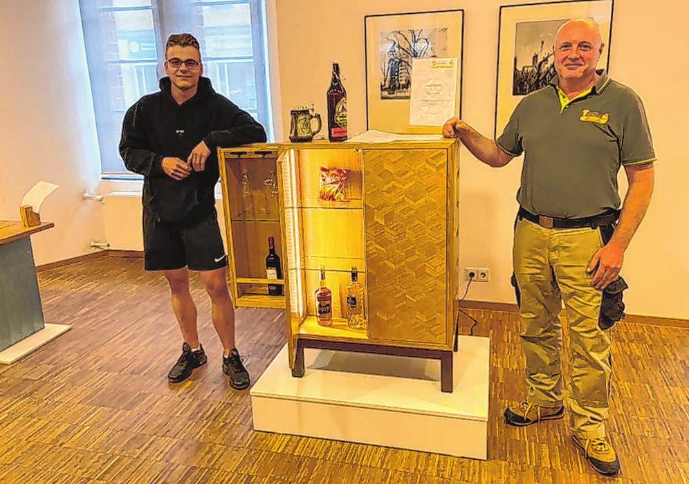 Gemeinsam stolz auf das Erreichte: Laurin Rockmann (li.) präsentiert sein gelungenes Gesellenstück - einen raffinierten Barschrank. Sein berufliches Rüstzeug erhielt er bei Meister Schoppe.