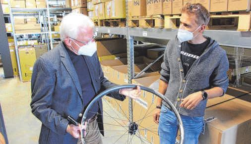 """Stadtrat Rolf Engler lässt sich die Eigenschaften einer 500 Euro teuren Carbonfelge erklären. """"Sie hält Sprüngen bis zu zehn Metern stand"""", sagt Assfalg."""