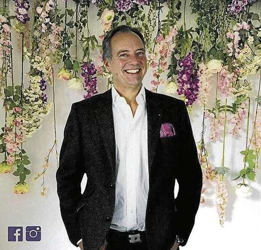 """Meislahn-Inhaber Daniel Hacker vor der """"Flower Wall"""". FOTO: MEISLAHN"""