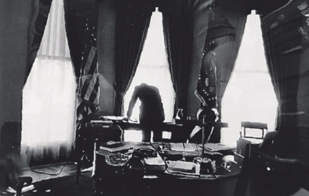 JFK beugt sich im Oval Office über Briefe. Bild: J. Lowe