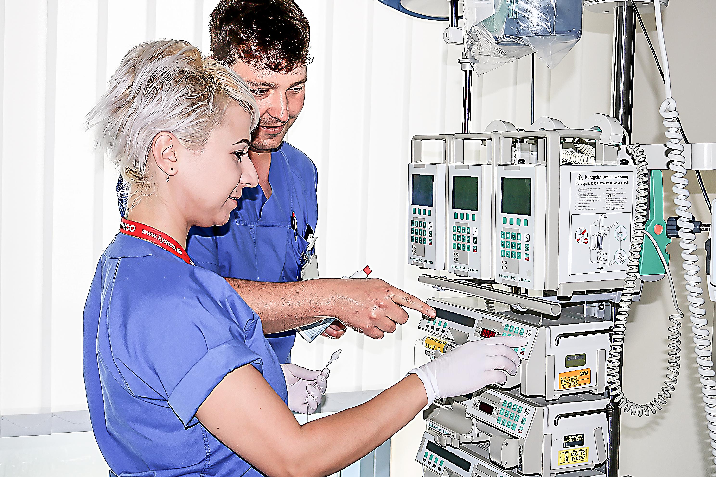 Lehrer Patrick Welzel erklärt Pflegeschülerin Vladyslava Degtiarova die Funktion der Perfusoren, eine Dosierpumpe zur Verabreichung von Medikamenten über den Tropf