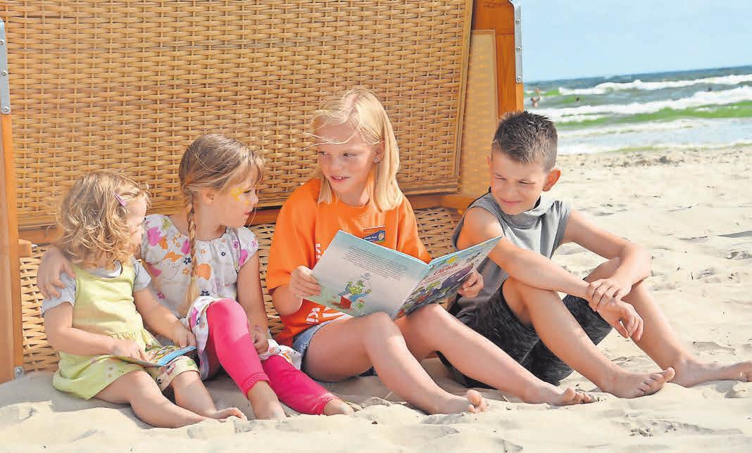 Kinderkurdirektorin Amelie im orangen Karlshagener Look bietet unter anderem Lesestunden am Strand an. Foto: KV Karlshagen