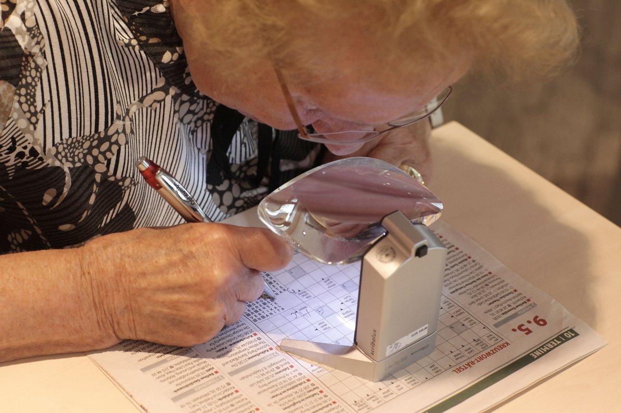 Eine sehbehinderte Frau löst Kreuzworträtsel. Eine Licht-Lupe erleichtert ihr dabei das Erkennen der Schrift.FOTO: DBSV/A. FRIESE
