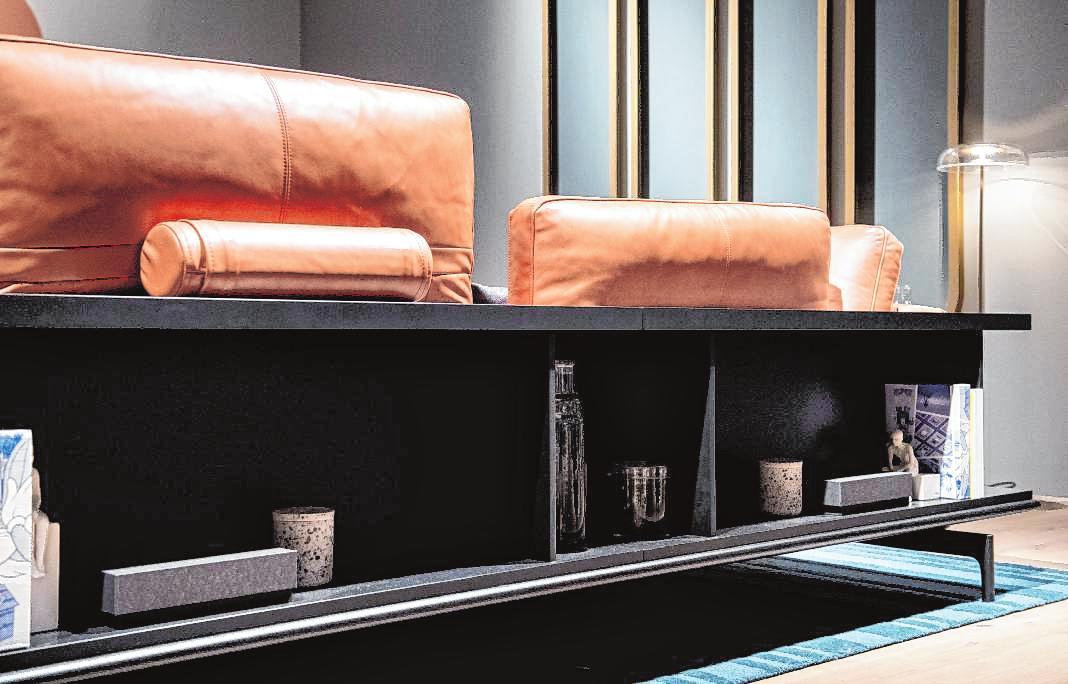 Die neuen Möbel haben Mehr-Wert : Die Rückwand des Sofas Liv von Rolf Benz etwa ist in dieser Ausführung des Systems ein offenes Regal (Bild links). Und die Armatur von Naber lässt sich um 90 Grad abkippen und im Spülbecken absenken. Mit einem Holzbrett darüber ist die Spüle als Arbeitsfläche nutzbar (Bild rechts).