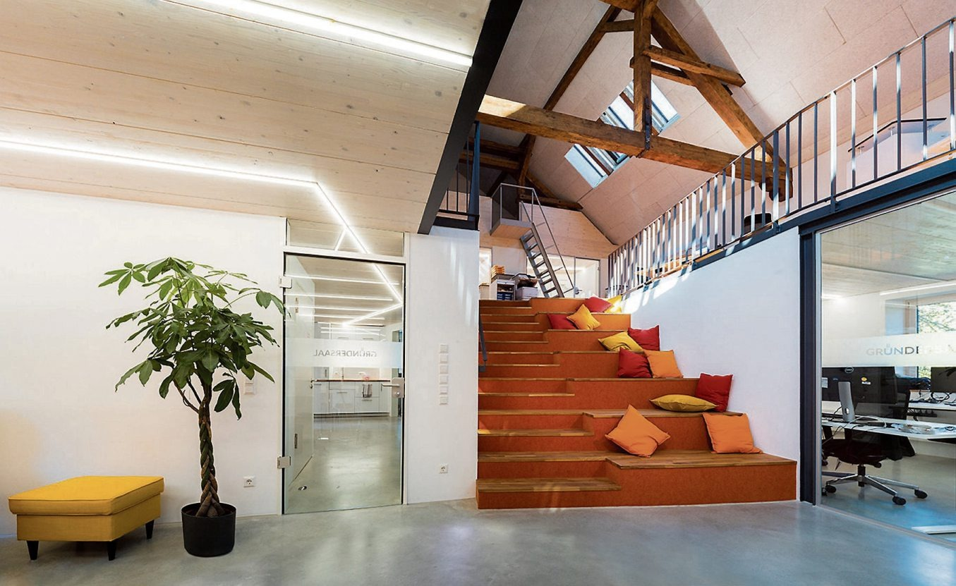 Impressionen aus dem Gründersaal: Ganz oben die Holztreppe, die bei Veranstaltungen als Sitzfläche genutzt werden kann, links darunter ein Blick auf die Galerie und die freigelegten Dachbalken, rechts ein Meetingraum als Ort für kreative Kommunikation. Bilder: COWORK GROUP GmbH