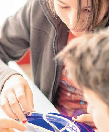 Spielerisches Lernen: Kinder puzzeln die Scherben eines irdenen Tellers zusammen.