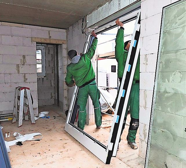 Auf der Baustelle setzen die Fachleute einen Fensterrahmen in die Maueröffnung
