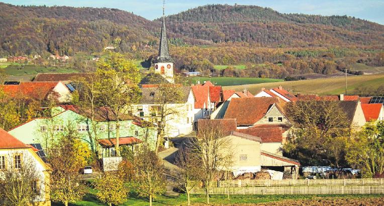 Die Ortsansicht von Happertshausen aus Richtung Aidhausen mit den Haßbergen im Hintergrund.