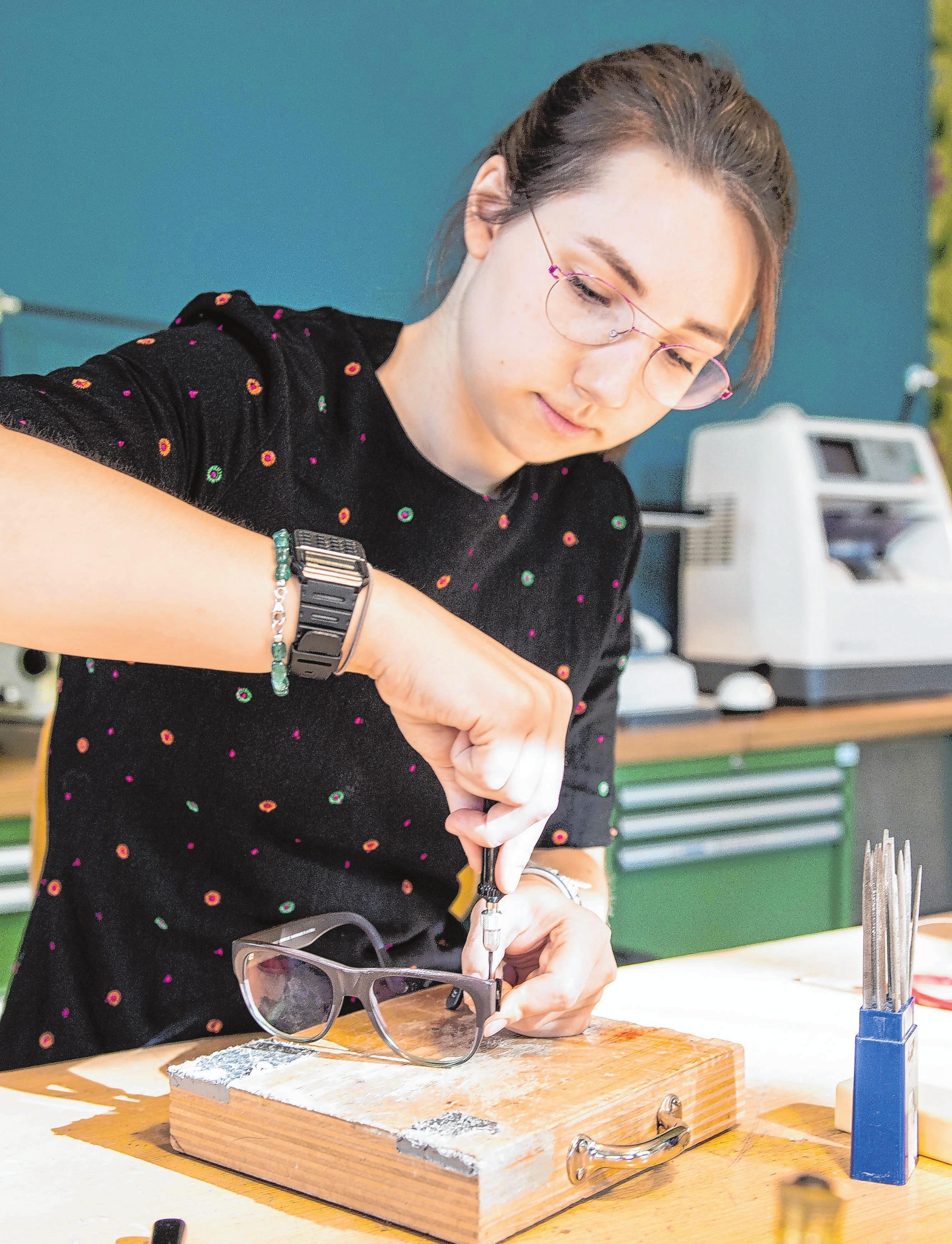 Mit Werkzeugen eine Brille bearbeiten: Diese Arbeiten erfordern Präzision und Konzentration.