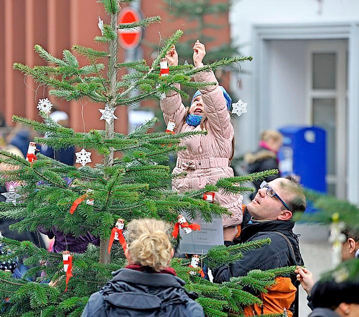 Kinder schmücken wieder Tannenbäume in der Stadt.