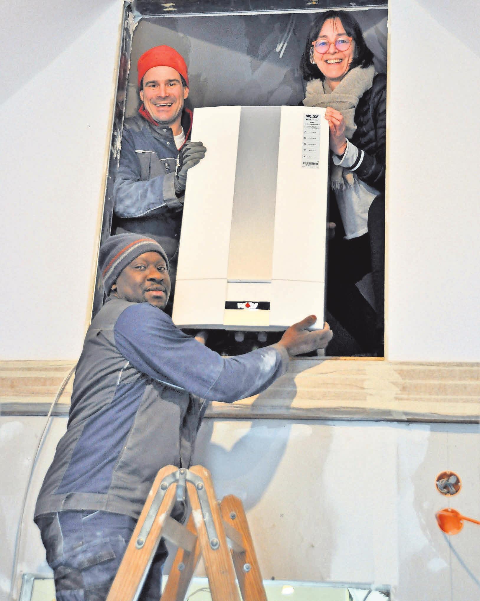 Astrid Dodenhoff packt tatkräftig mit an, als Volker Hielscher (oben) und Alain Idado die neue Heizung auf den Dachboden heben. Aktuell sind die Mitarbeiter der Firma Heitmüller dabei, diverse Heizungsrohre im alten Feuerwehrgerätehaus zu verlegen.