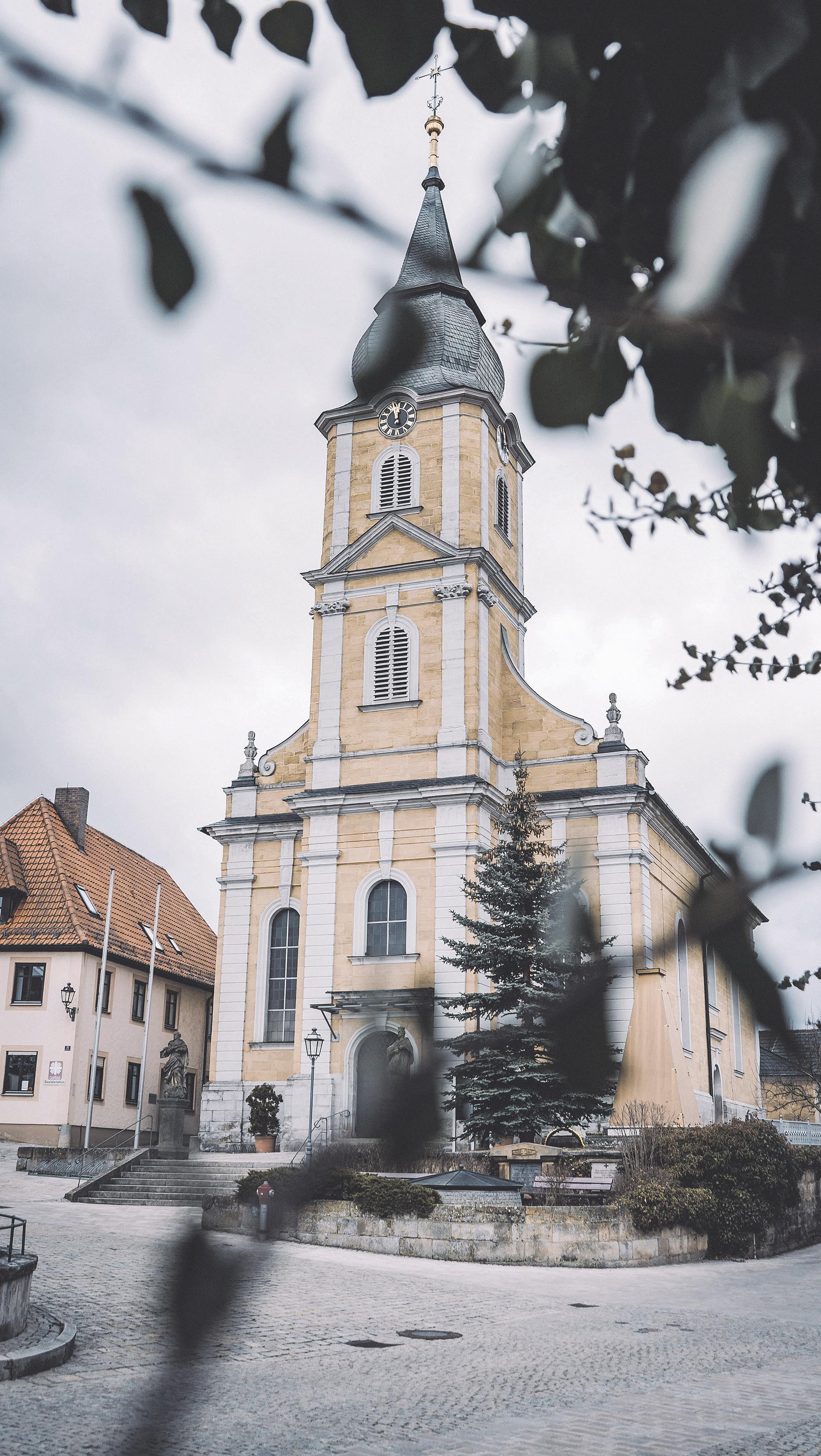 """Die katholische Pfarrkirche """"St. Heinrich und Kunigunde"""" zeigt sich als klassizistische Saalkirche mit eingezogenem Chor und Einturmfassade. Foto: Pia Nowak"""