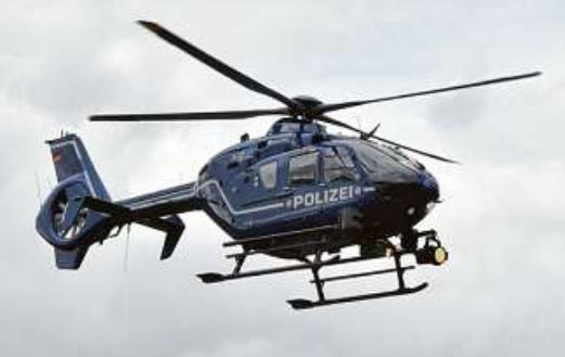 Suche aus der Luft: fliegende Polizisten im Hubschrauber über Berlin. PA/PAUL ZINKEN
