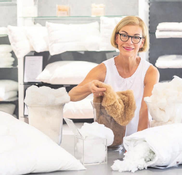 Regina Rosenbaum mit hochwertigem Kamelhaar und anderen Füllmaterialien in der Zudeckenabteilung vom bettenhaus welge. Foto: Urte Bösche