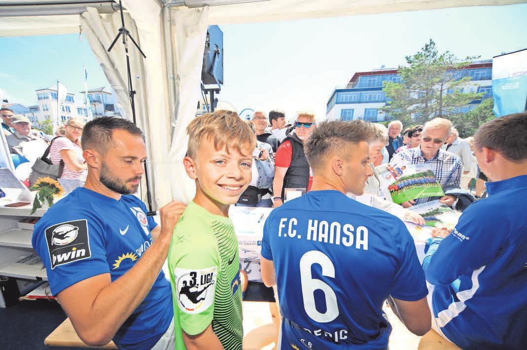 Abwechslung: Bei der Warnemünder Woche waren Pascal Breier, Mirnes Pepic und Frederik Lach (v.l.) zu Gast beim Sportbuzzer-Aktionstag der OZ. John (9) aus Rostock ließ sich ein Trikot signieren. Foto: Ove Arscholl