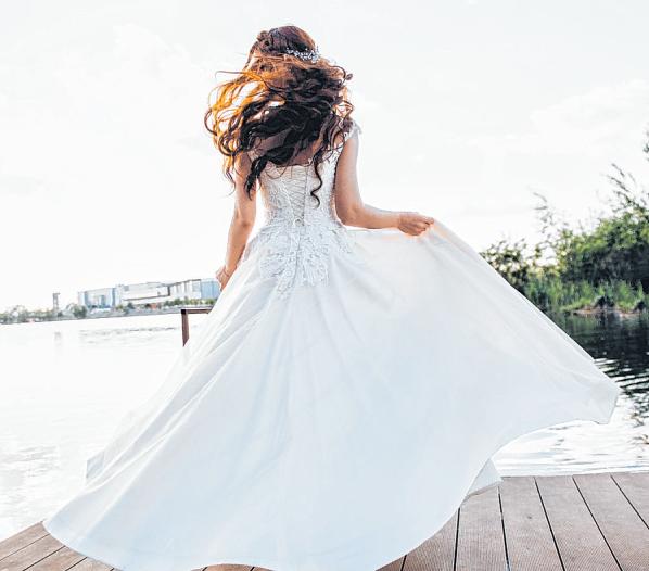Eine Braut will auf einem Steg für das Hochzeitsfoto posieren. Sie hat sich für ein langes Kleid im Romantikstil entschieden. Foto: Kateryna
