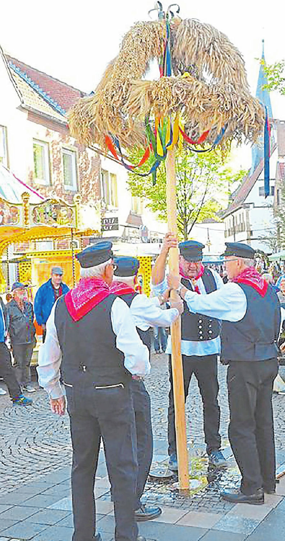 Die Männer der Kötterfamilie stellen zu Beginn des Erntedankmarkts die Erntekrone auf. Foto: Rainer Nix