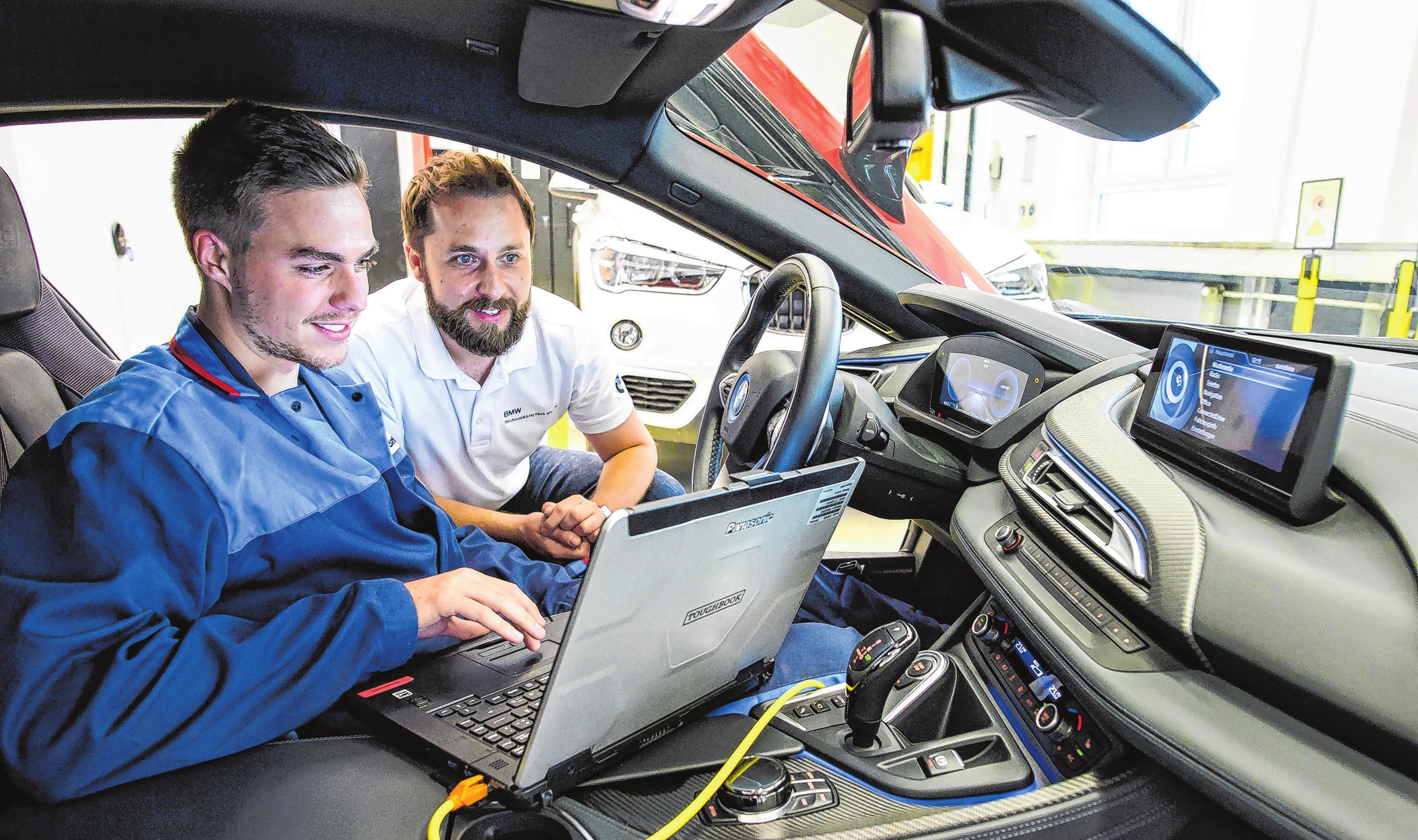Keine reine Schrauberei: Kfz-Mechatroniker wie Andreas Batki (l, mit Ausbilder Florian Pachur) müssen auch sicher mit Computern umgehen können. Fotos: Jörg Koch/dpa-mag