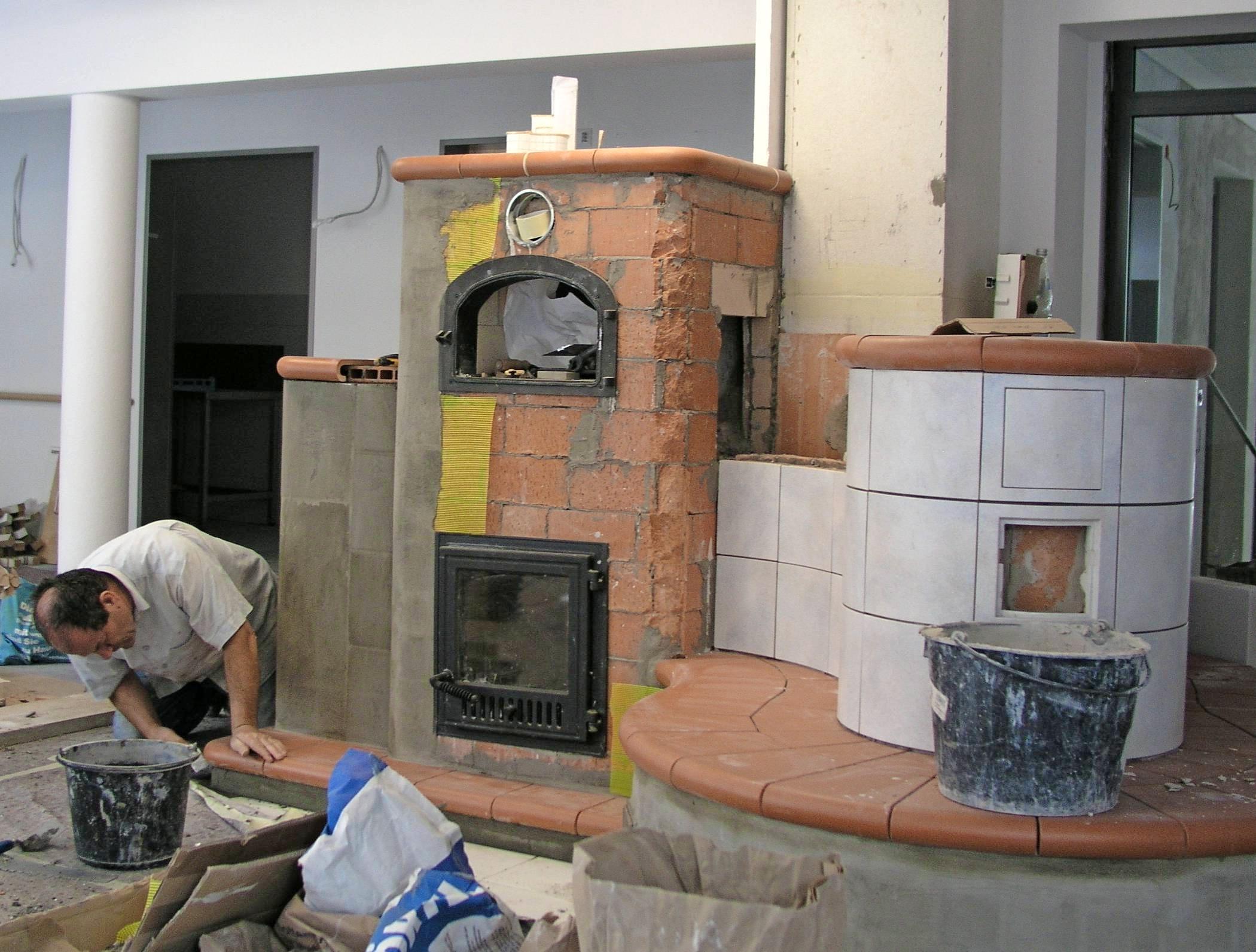 Der Bau eines Kachelofens ist aufwendig. Dafür hält der länger warm als ein Kaminofen (Bild unten). Fotos: dpa