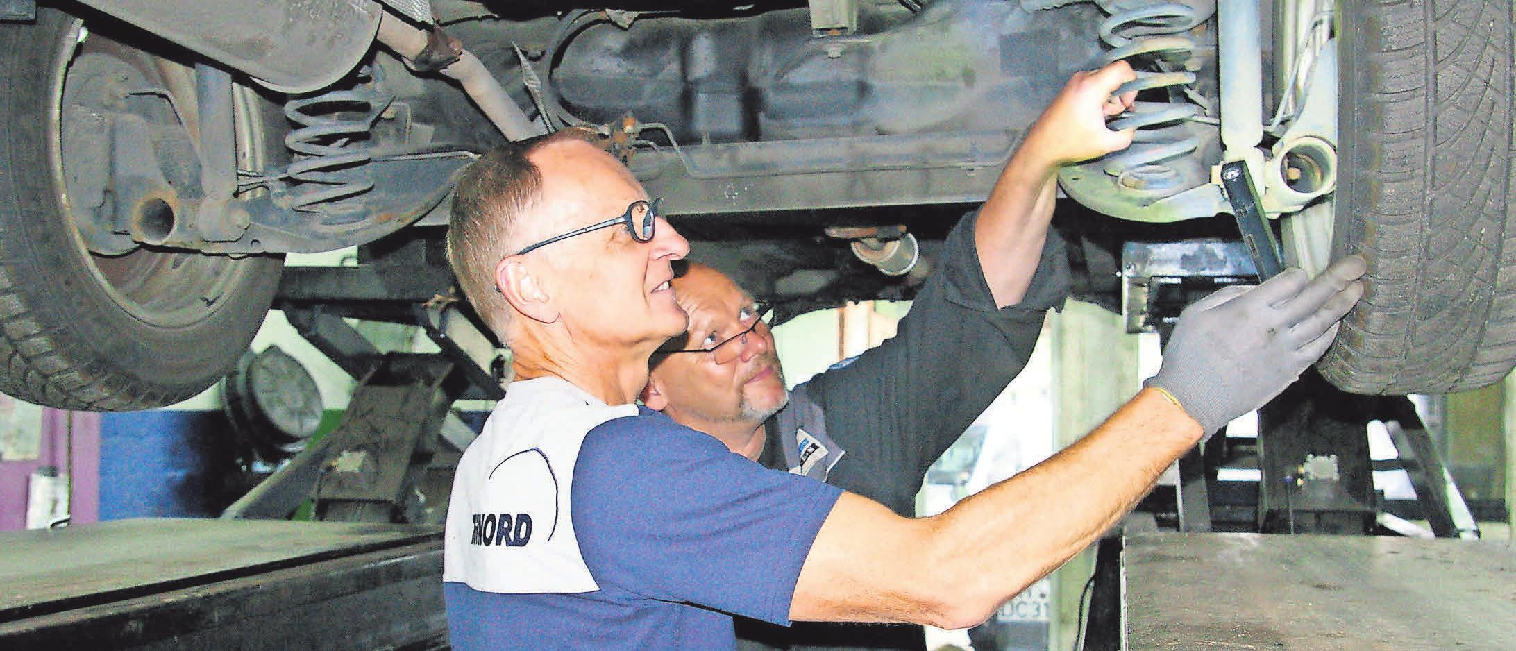 Uwe Ehrhardt vom TÜV Nord (links) und Firmenchef Torsten Bode untersuchen ein Fahrzeug.