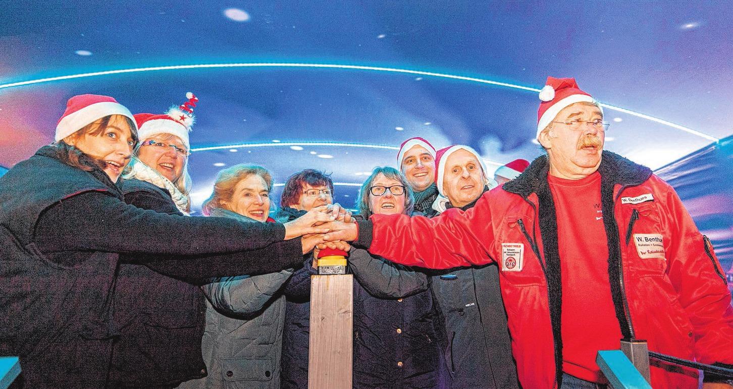 Spannungserwarteter Moment: Mit dem Drücken des roten Buzzers wird die Weihnachtsbeleuchtung auf dem Brücker Marktplatz eingeschaltet. Foto: König