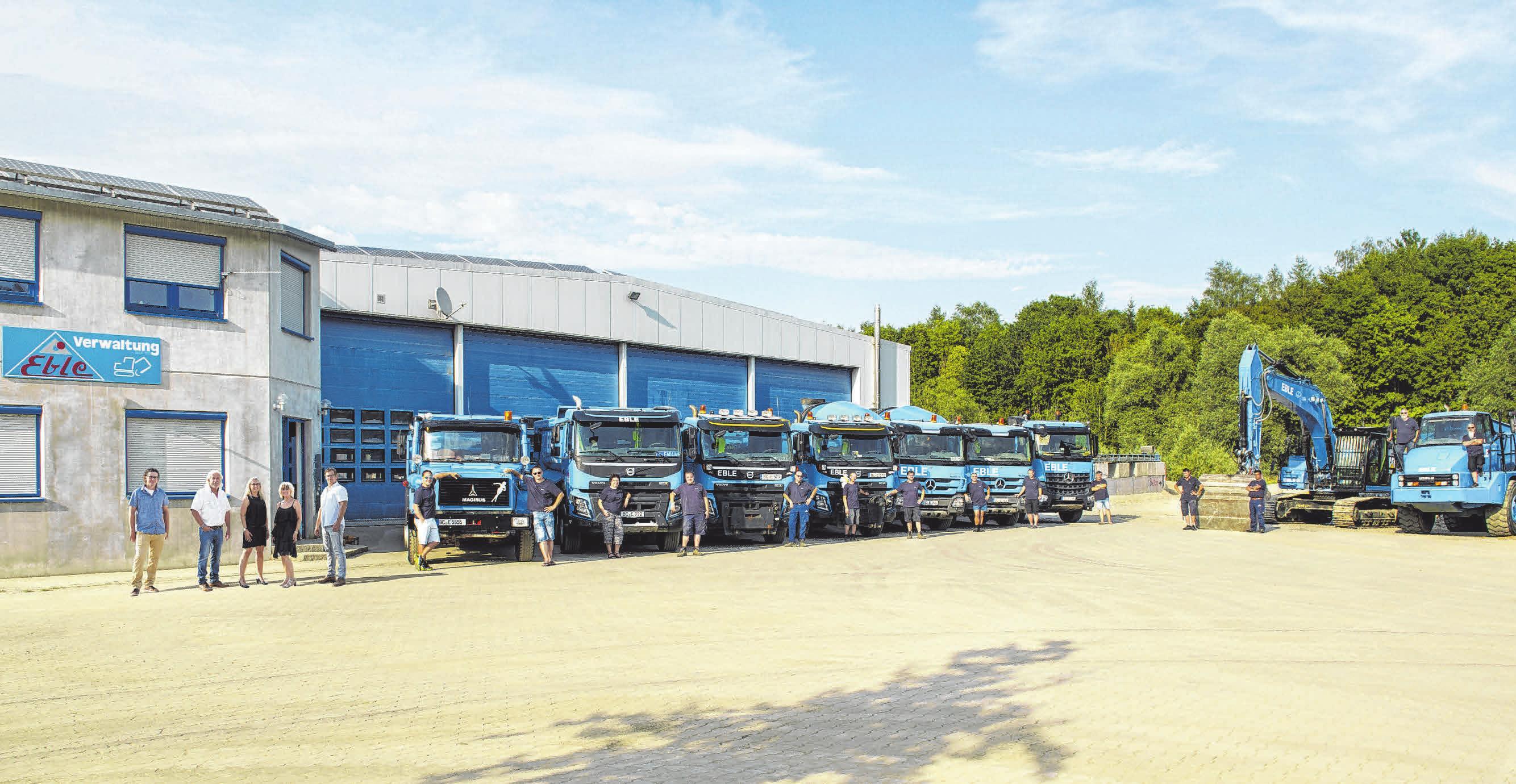 Die Familie Eble präsentiert sich mit ihren Mitarbeitern und ihrem Fuhrpark vor dem neuen Firmengebäude. FOTO: PRIVAT