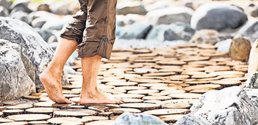 Auf blanken Sohlen übers Holz: Barfußgehen soll laut Kneippscher Lehre unter anderem das Immunsystem stärken. Foto: Bad Wörishofen