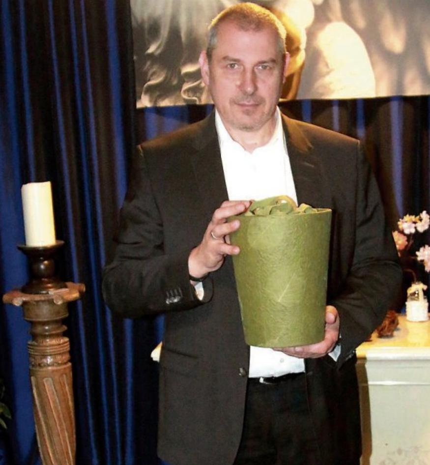 Roberto Seifert mit einer Naturstoffurne aus handgeschöpftem Loktapapier. Bild: Stefan Zibulla