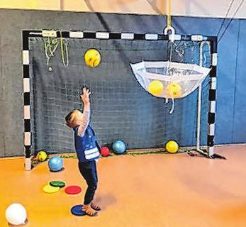 Kreative Ideen gehören zum Alltag beim Kindersport. Hier hilft ein Schirm als Ballfanganlage.